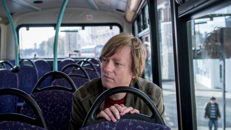 Michel Faber sits on (what looks like) a Lothian Bus in Edinburgh
