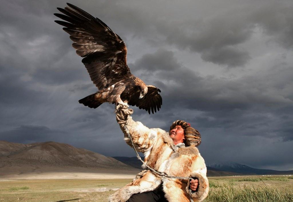 Portrait of Kazakh man and a Golden Eagle in Mongolia. Ulgii Province. Mongolia.